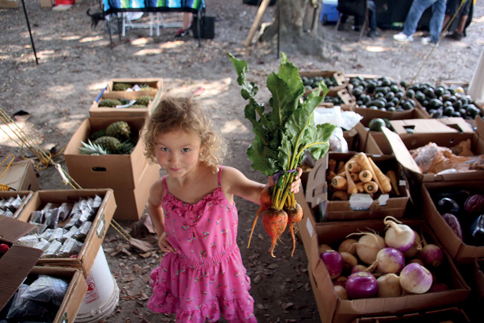 little girl holding up a bunch of fresh beets at a farmer's market
